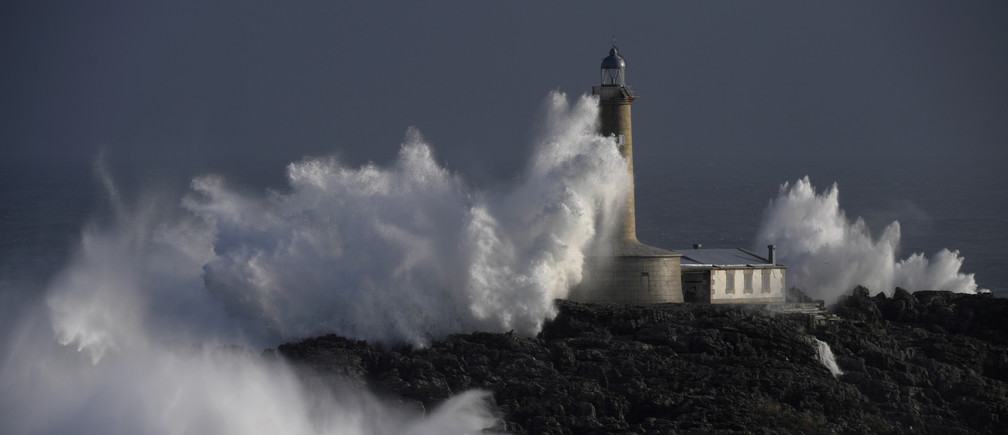 "Waves crash on the lighthouse of ""La Isla del Mouro"" in the port town of Santander in Spain, January 17, 2018."