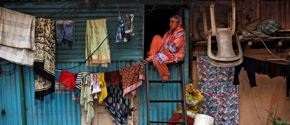 "A woman sits on a ladder installed outside her house, during a nationwide lockdown in India to slow the spread of COVID-19, in Dharavi, one of Asia's largest slums, during the coronavirus disease outbreak, in Mumbai, India, April 13, 2020. REUTERS/Francis Mascarenhas      SEARCH ""CORONAVIRUS MUMBAI SLUM"" FOR THIS STORY. SEARCH ""WIDER IMAGE"" FOR ALL STORIES. - RC2Z7G96ATBG"