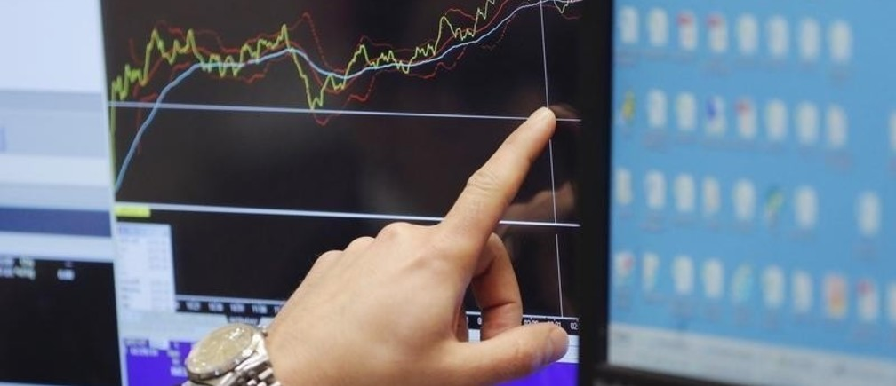 A trader points at a chart on a monitor above the floor of the New York Stock Exchange in New York December 30, 2015