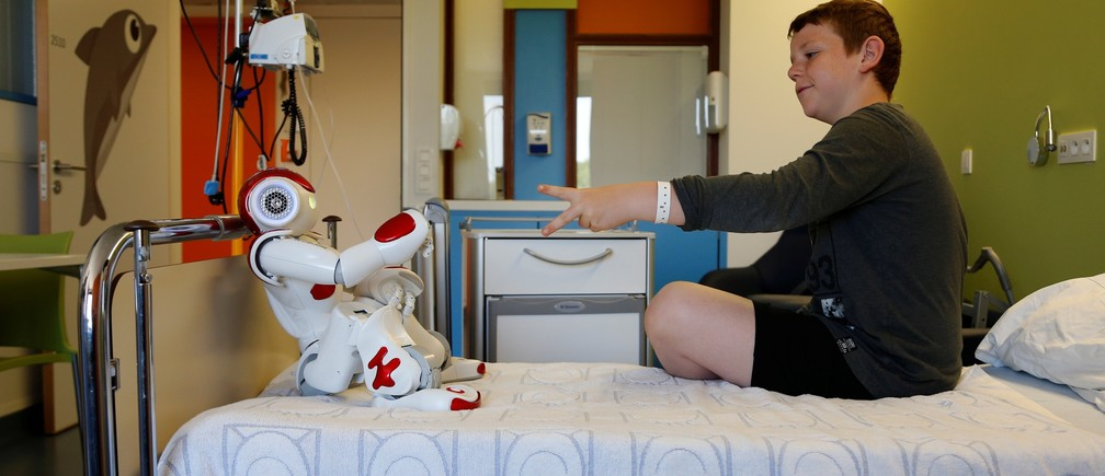 "Belgian Ian Frejean, 11, plays with ""Zora"" the robot, a humanoid robot designed to entertain patients and to support care providers, at AZ Damiaan hospital in Ostend, Belgium June 16, 2016."