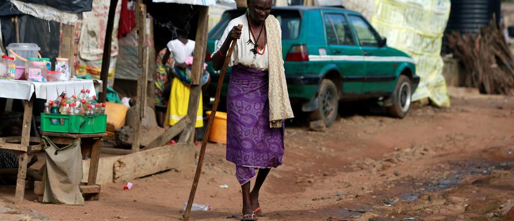 Una mujer camina con la ayuda de un bastón en el campamento de desplazados internos de Kuchingoro, mientras el gobierno sigue conteniendo la propagación de COVID-19 en Abuja, Nigeria, el 20 de junio de 2020.