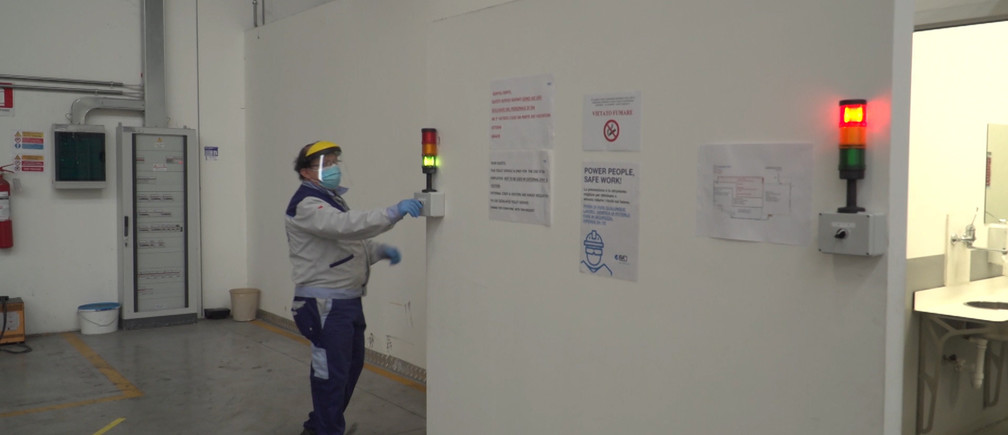 A worker is seen by a traffic light limiting the access to bathrooms inside the ISA factory that has introduced new safety measures to respect social distancing among workers to stop the spread of the coronavirus disease (COVID-19) in Bastia Umbra, Italy, April 22, 2020, in this still image taken from video. REUTERS TV via REUTERS - RC2BAG9Z9LJB