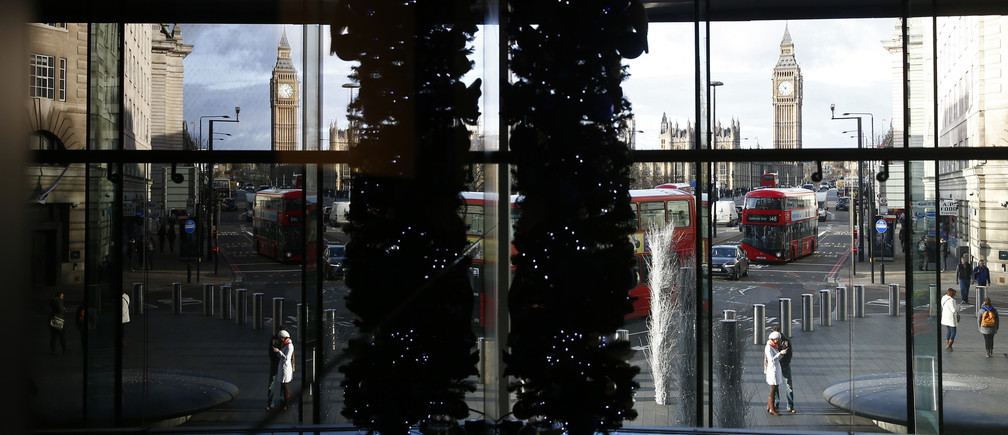 Big Ben and the Houses of Parliament are seen through a window in central London December 23, 2014.