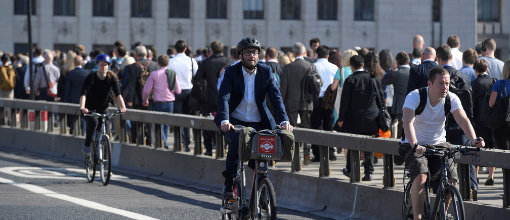 Workers cross London Bridge by foot and bicycle during the morning rush hour in London, Britain, June 13, 2017. REUTERS/Toby Melville - RC175390F860