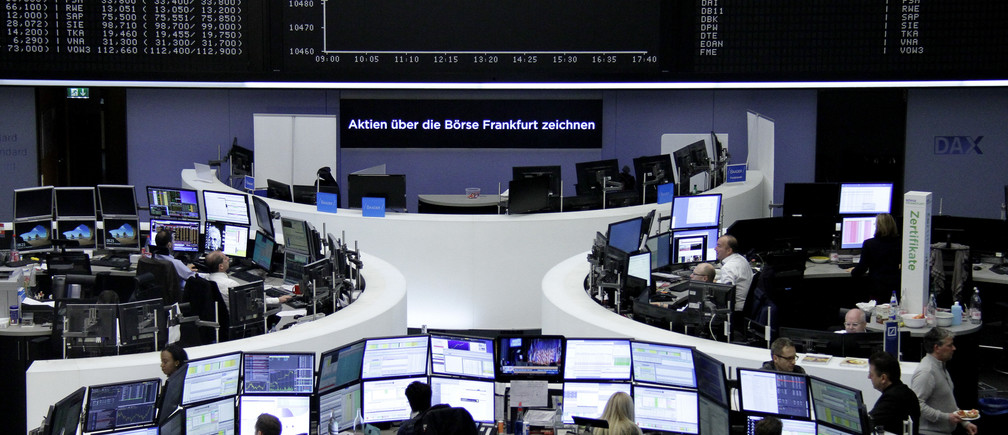 Traders work at their desks in front of the German share price index, DAX board, at the stock exchange in Frankfurt, Germany, early November 9, 2016. REUTERS/Staff/Remote - RTX2SPEC