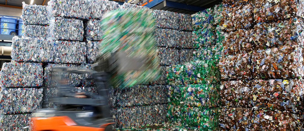 A long exposure shows a forlklift lifting up a bundle of pressed bottles made from PET (polyethylene terephthalate) plastic at Transcycle Transport & Recycling AG company in Neuenhof, Switzerland November 22, 2018. Picture taken November 22, 2018.   REUTERS/Arnd Wiegmann - RC17A8FE5410
