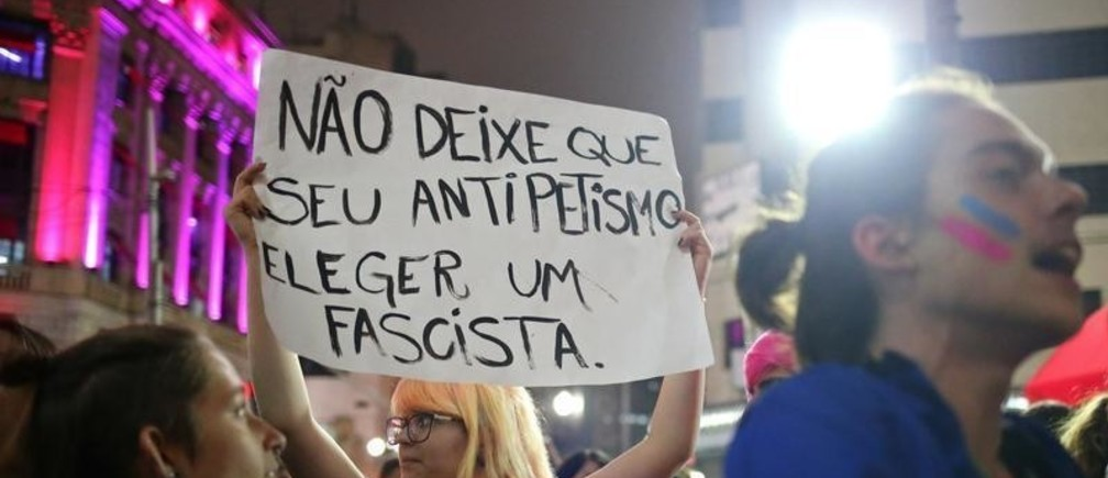 """Demonstrators shout slogans against Jair Bolsonaro, far-right lawmaker and presidential candidate of the Social Liberal Party (PSL), during a protest called """"against fascism"""" in Sao Paulo, Brazil October 11, 2018. The poster reads: """"Don't allow your anti-Workers Party (PT) to elect a fascist."""""""