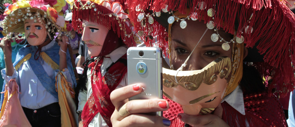 A parishioner takes pictures with her cell phone during the feast in honour of Saint Sebastian, patron saint of Diriamba, about 45 km (28 miles) south of Managua, January 19, 2011. The masks worn by the revellers were first used in the 16th century by the local indigenous habitants in a theatrical parody in which they mocked Spanish conquistadores