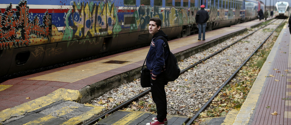 A passenger waits before boarding a train bound for Athens at Lianokladi railway station in central Greece November 29, 2012. Once an unpopular travel option, Greece's slow and creaky trains are winning new fans for the first time in decades as Greeks struggling with soaring fuel prices and high road taxes leave their beloved cars at home. Picture taken November 29, 2012. REUTERS/Yorgos Karahalis (GREECE - Tags: TRANSPORT SOCIETY BUSINESS) - RTR3BIZC