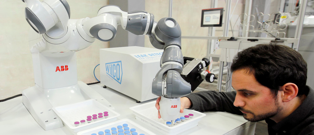 Engineer Manel Trilla of Swiss power technology and automation group ABB adjusts an arm of a YuMi - IRB14000, a collaborative dual-arm industrial robot, of ABB Robotics at a plant in Baden, Switzerland February 7, 2019. REUTERS/Arnd Wiegmann - RC19D3E3DF30