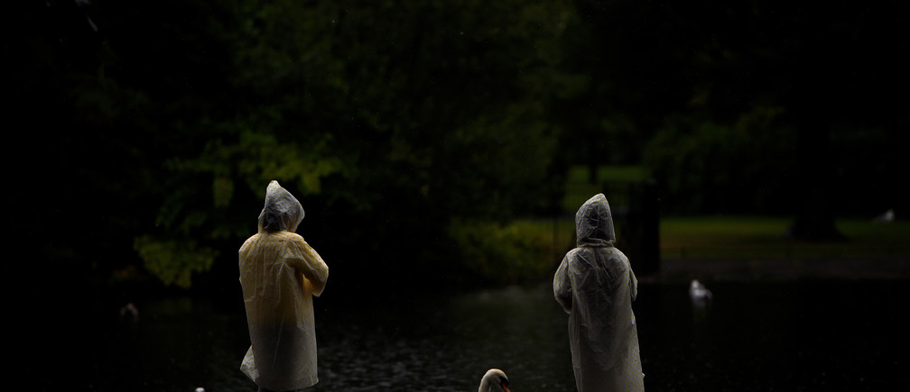 """People in raincoats look at a swan in St. Stephen's green during heavy rain in Dublin, Ireland, August 14, 2017. REUTERS/Clodagh Kilcoyne  SEARCH """"KILCOYNE SUMMER"""" FOR THIS STORY. SEARCH """"WIDER IMAGE"""" FOR ALL STORIES. - RC158D3F8DD0"""