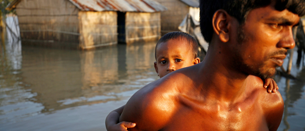 A child reacts to the camera while sitting on his father back as they make their way in a flooded area in Bogra, Bangladesh.