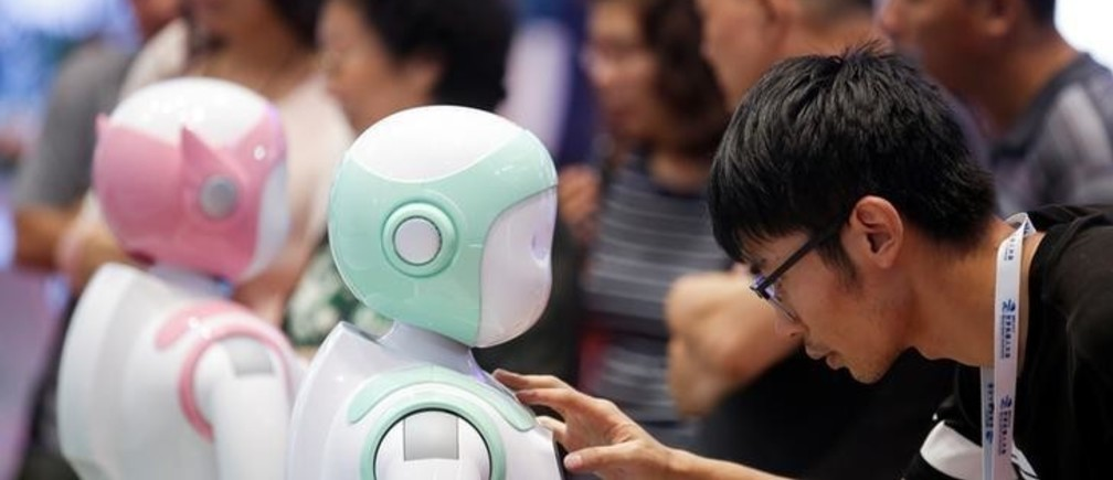 A man programs an iPal Companion Robot by Nanjing Avatar Mind Robot Technology at the 2017 World Robot conference in Beijing, China August 22, 2017.   REUTERS/Thomas Peter
