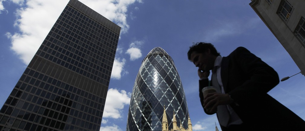 A man passes the Swiss RE building, also known as the Gherkin, in the financial district City of London June 22, 2010. Britain's Chancellor of the Exchequer George Osborne announced the harshest budget in a generation on Tuesday, promising to bring a record budget deficit of 11 percent of GDP down to 1 percent in 5 years. REUTERS/Luke MacGregor (BRITAIN - Tags: BUSINESS POLITICS) - LM1E66M17EI01