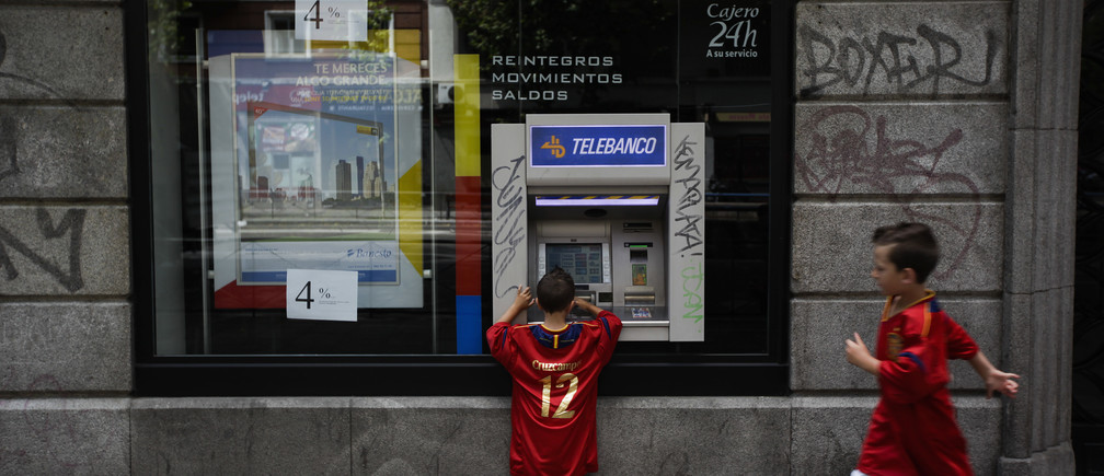 German Herrero Sanjuan, 9,  approaches his brother Fernando, 5, as he plays with a Banesto bank ATM machine in Madrid July 1, 2012. They are both wearing Spanish national soccer team jerseys to show support for their team ahead the Euro 2012 final soccer match between Spain and Italy tonight. REUTERS/Susana Vera (SPAIN - Tags: SPORT SOCCER) - GM1E8711KJR01