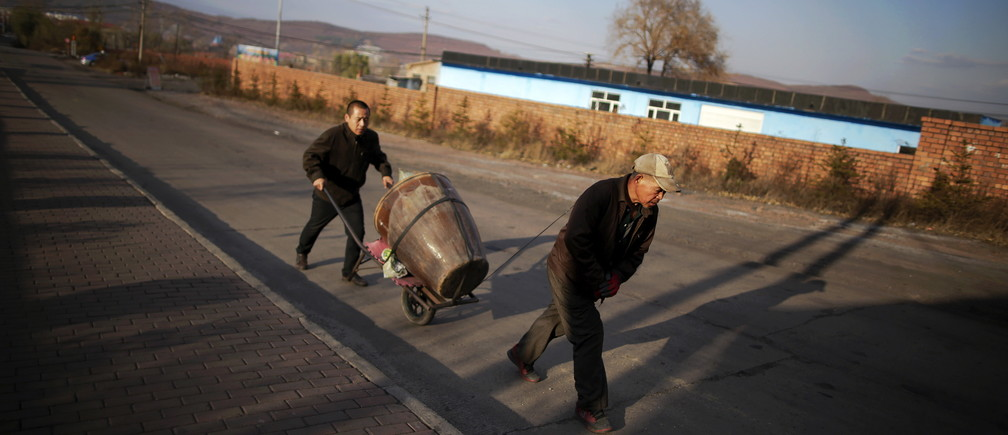 Miners carry their supplies for upcoming winter, towards a coal mine from the state-owned Longmay Group, on the outskirts of Jixi, in Heilongjiang province, China, October 24, 2015. To match story CHINA-COAL/JIXI     Picture taken on October 24, 2015. REUTERS/Jason Lee - GF20000045470