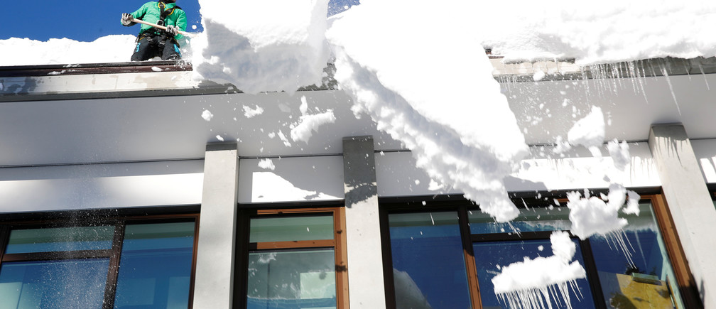 A worker removes snow from the roof of a building in Davos, Switzerland January 15, 2019. REUTERS/Arnd Wiegmann - RC13E89D4B60