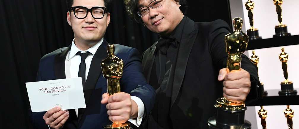 """Bong Joon Ho and Han Jin Won hold their Oscar statues for Original Screenplay for """"Parasite"""" at the 92nd Academy Awards in Hollywood, Los Angeles, California, U.S., February 9, 2020. Matt Petit/A.M.P.A.S./Handout via REUTERS ATTENTION EDITORS. THIS IMAGE HAS BEEN SUPPLIED BY A THIRD PARTY. NO MARKETING OR ADVERTISING IS PERMITTED WITHOUT THE PRIOR CONSENT OF A.M.P.A.S AND MUST BE DISTRIBUTED AS SUCH. MANDATORY CREDIT. - RC2JXE9RMRRB"""