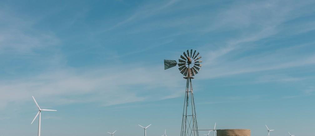wind vane on grass field wind power turbine renewable clean air blue sky future green