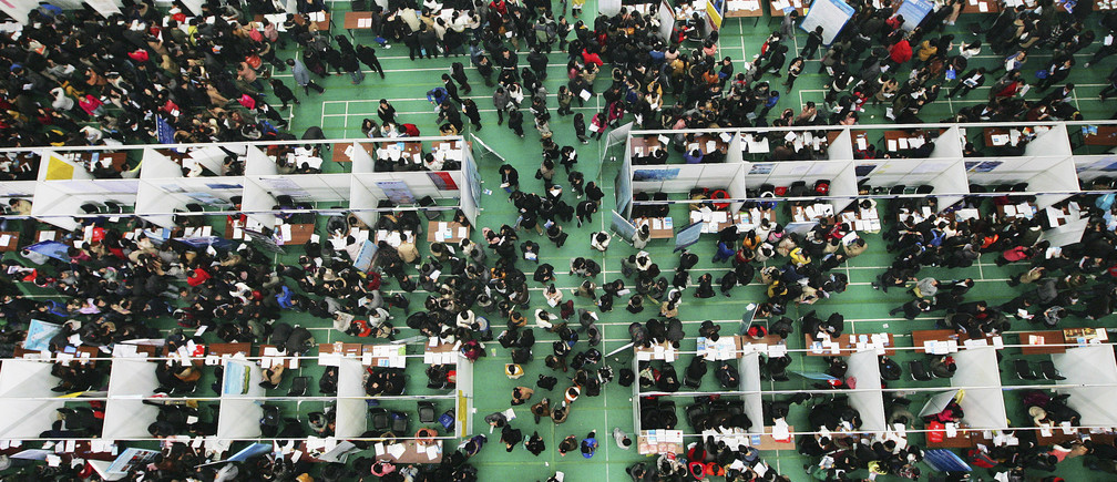 Job seekers attend a job fair at Tianjin University November 22, 2013. According to local media, more than 6,000 people rushed to the job fair on Friday for openings from 300 companies against the backdrop that a decrease is expected in available positions for fresh graduates in the China job market in 2014