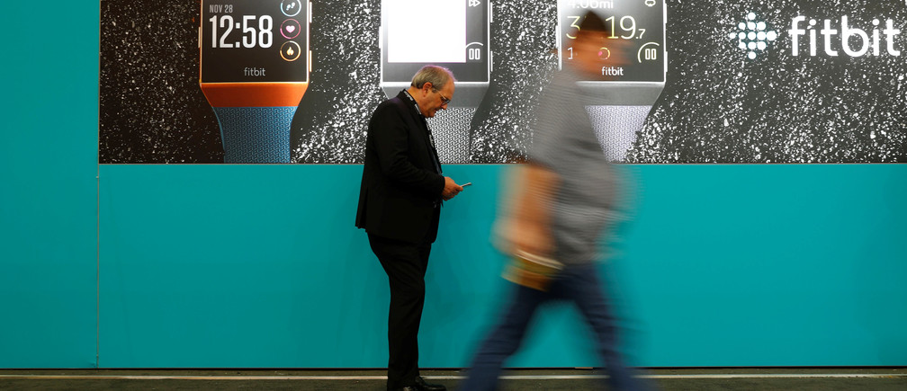 Visitors walk past an advertising billboard for Fitbit Ionic watches at the IFA Electronics Show in Berlin, Germany, September 1, 2017.    REUTERS/Fabrizio Bensch - RC16DFBD5800
