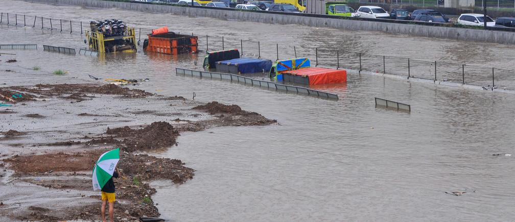 Trucks are seen partially submerged along the Jakarta-Cikampek Toll Road in Bekasi, near Jakarta, Indonesia February 25, 2020.