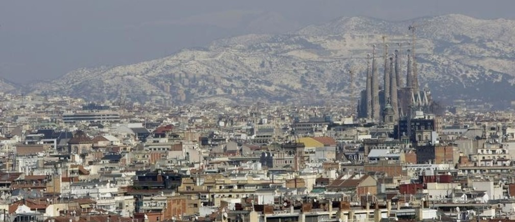 Gaudi's Sagrada Familia and Barcelona's skyline are seen against the backdrop of a snow-covered mount after a snowstorm March 9, 2010.  REUTERS/ Albert Gea (SPAIN - Tags: ENVIRONMENT CITYSCAPE) - GM1E6391P7R01