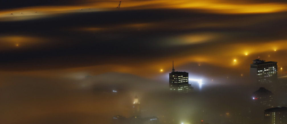 A long exposure picture shows a seasonal fog illuminated by the lights of Cape Town harbour
