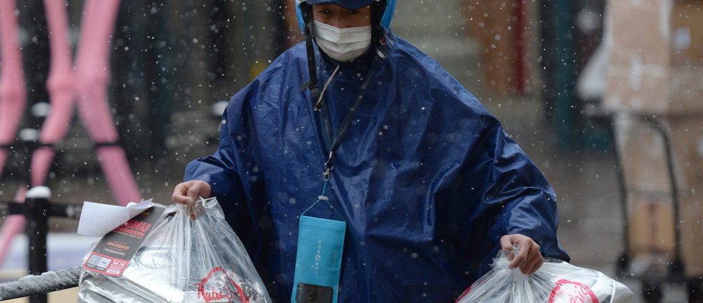 An Ele.me deliveryman wearing a face mask delivers food amid snowfall, following an outbreak of the novel coronavirus in the country, at a shopping area on Valentine's Day in Beijing, China February 14, 2020. REUTERS/Tingshu Wang - RC2A0F9AMN2V