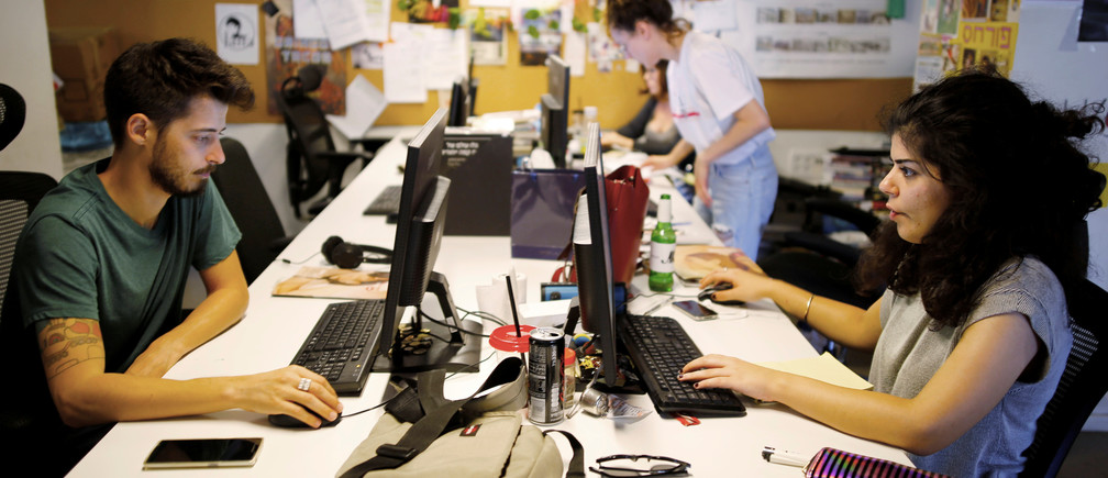"""Employees work at the offices of """"Time Out Tel Aviv"""" magazine in Tel Aviv, Israel September 28, 2017. Picture taken September 28, 2017. REUTERS/Amir Cohen - RC1C045AA690"""
