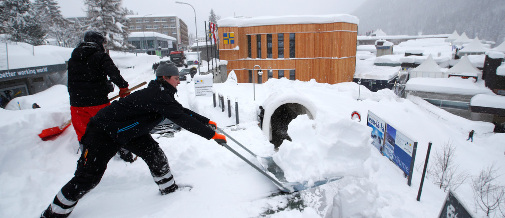Staff clear snow ahead of the World Economic Forum's Annual Meeting, January 2018