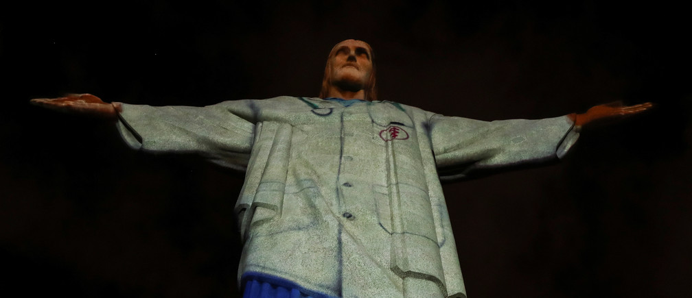 """La estatua del Cristo Redentor está iluminada con una imagen del atuendo de un personal sanitario y la palabra """"gracias"""" durante los eventos del Domingo de Pascua, en medio del brote de la enfermedad coronavirus (COVID-19), en Río de Janeiro, Brasil, el 12 de abril de 2020."""