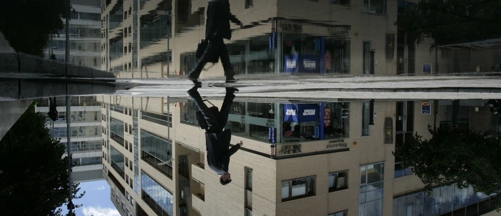 A businessman avoids puddles at the International Financial Services Centre - the business district of Dublin May 27, 2007. Picture was rotated 180 degrees. REUTERS/Luke MacGregor (IRELAND) - RTR1QETN