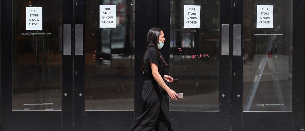 A woman wearing a face mask walks past a closed shop after the reopening of retail stores, amid the spread of the coronavirus disease (COVID-19), in London, Britain June 16, 2020. REUTERS/Hannah McKay - RC2DAH98Q9D9