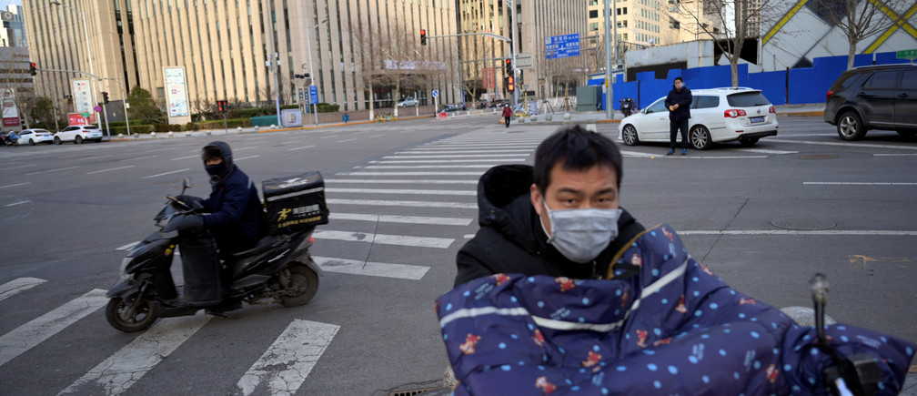 Delivery workers wearing face masks ride scooters, as the country is hit by an outbreak of the novel coronavirus, in Beijing's central business district, China February 18, 2020. REUTERS/Tingshu Wang - RC203F9M08BQ