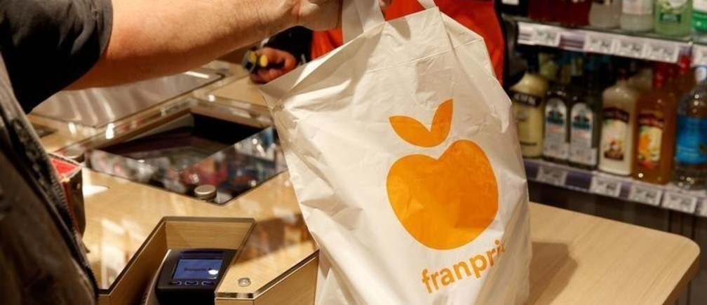"""A customer holds a plastic bag at a Franprix store, the convenience store chain which is part of retailer Casino, after it was upgraded to their new """"Mandarine"""" concept in Paris, France, April 11, 2016.  REUTERS/Philippe Wojazer - D1AESXTWROAA"""