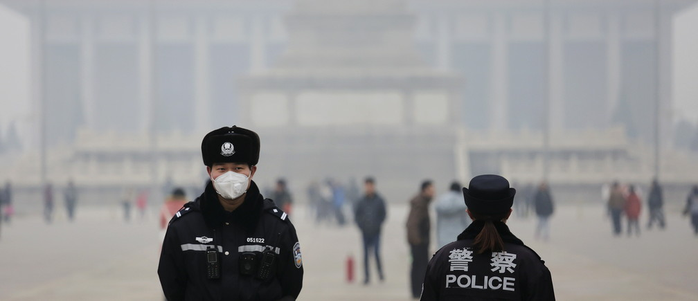 "Policemen wear masks protecting from extreme smog at the Tiananmen Square in Beijing December 8, 2015 as China's capital issues its first ever ""red alert"" for pollution. REUTERS/Damir Sagolj - GF10000258348"