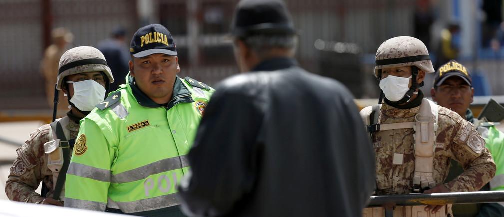 Un hombre habla con un policía en la frontera entre Perú y Bolivia después del anuncio del gobierno peruano del cierre de la frontera en un intento de frenar la propagación del nuevo coronavirus (COVID-19), en Desaguadero, Bolivia, el 17 de marzo de 2020.