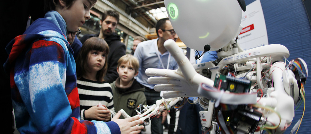 Children interact with the humanoid robot Roboy at the exhibition Robots on Tour in Zurich, March 9, 2013. A project team composed of scholars and industry representatives developed the prototype of the tendon driven humanoid robot Roboy within nine months.  Roboy was unveiled to the public today during the exhibition that is marking the 25th anniversary of the Artificial Intelligence Laboratory of the University of Zurich (AI Lab). Picture taken with fish-eye lens. REUTERS/Michael Buholzer (SWITZERLAND - Tags: SCIENCE TECHNOLOGY SOCIETY BUSINESS) - RTR3ERWR
