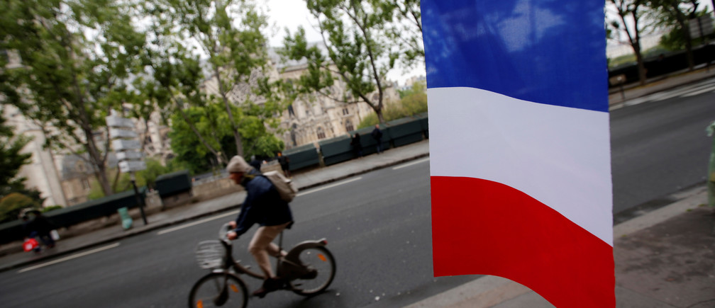 A cyclist passes a French flag on the eve of the French presidential election in Paris, France, May 6, 2017REUTERS/Jean-Paul Pelissier - RC1FF4FA7070