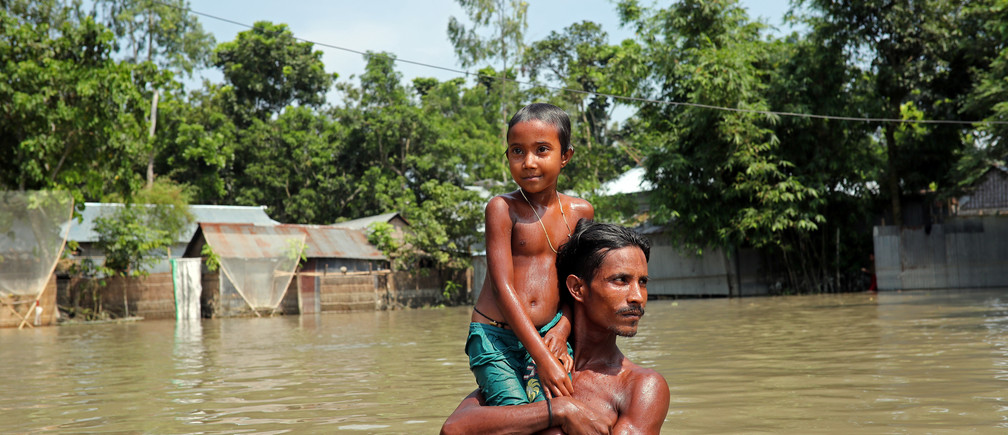 Flood-affected people wade through flooded water in Jamalpur, Bangladesh, July 21, 2019. REUTERS/Mohammad Ponir Hossain - RC196990A670