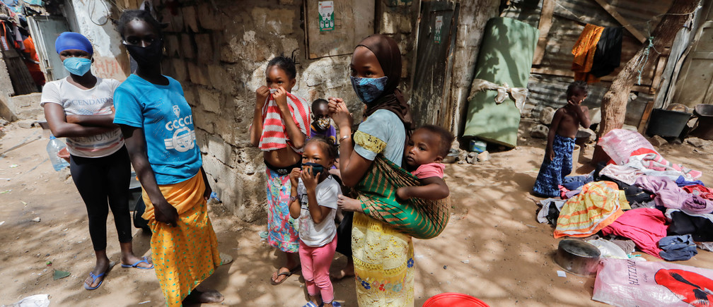 Children wearing face masks stand listening to their friends outside their shelters, amid the spread of the coronavirus disease (COVID-19), in Liberte 6 Baraka district of Dakar, Senegal May 2, 2020.