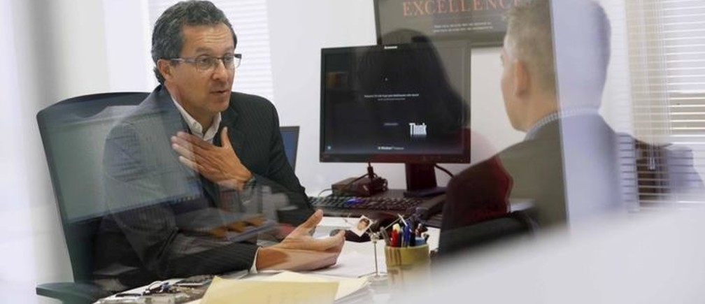Leonardo Lacruz (L), the Venezuela director of multinational headhunter Korn/Ferry, talks to a man, during an interview at his office in Caracas August 3, 2015. Headhunters across Latin America are tapping Venezuela for low-cost professionals as a deepening economic crisis has left many skilled workers earning less money than taxi drivers and waiters. Highly-trained Venezuelans are seeking to escape a decaying socialist economy in which they often have to work second jobs and spend hours in line to buy basic goods such as milk or diapers. Picture taken on August 3, 2015. REUTERS/Carlos Garcia Rawlins