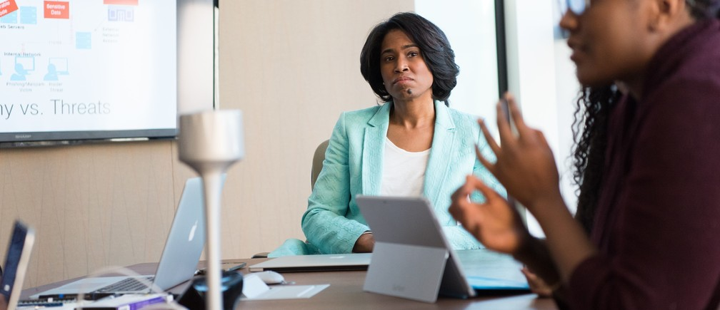selective focus photography of woman in gray blazer looking at woman in black top c-suite retention ceo managing direction recruitment