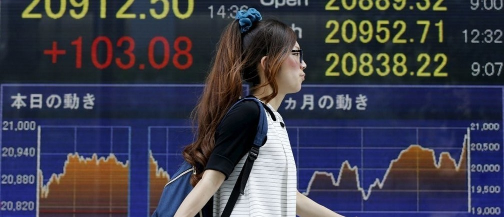 A woman walks past an electronic stock quotation board outside a brokerage in Tokyo June 24, 2015. Japan's Nikkei share average vaulted to the highest level since 1996, ramping up the gains to around 20 percent since the start of the year thanks to signs of a pick up in economic growth, earnings optimism and hopes Greece will avoid a debt default.