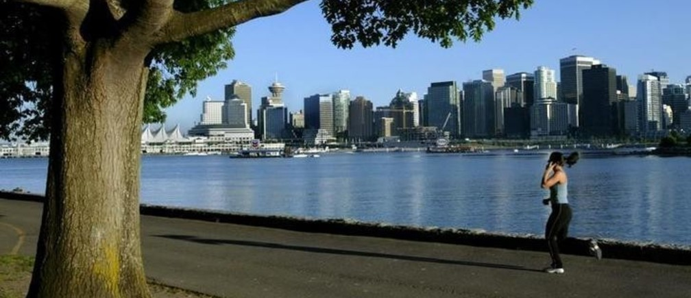 A jogger runs along the seawall in Stanley Park with the city skyline in thebackground in this June 24, 2003 photo. Vancouver was named host of the 2010Winter Olympics during voting in Prague July 2, 2003. In a close vote theIOC gave the bid to Vancouver by a score 56 to 53 over Pyeongchang, SouthKorea.  NO RIGHTS CLEARANCES OR PERMISSIONS ARE REQUIRED FOR THIS IMAGE REUTERS/Andy ClarkAC/AS