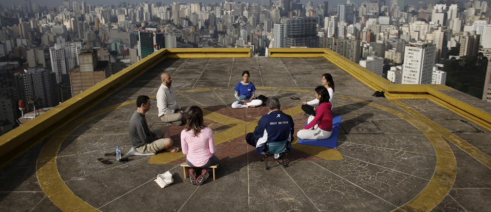 People meditate on the helipad of Copan building to celebrate World Health Day, which was observed on April 7, in downtown Sao Paulo April 9, 2015. REUTERS/Nacho Doce  - GF10000053642