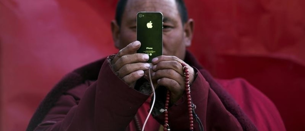 A Tibetan Buddhist monk takes pictures with his smartphone of a daily chanting session at a Buddhist laymen lodge during the Utmost Bliss Dharma Assembly, the last of the four Dharma assemblies at Larung Wuming Buddhist Institute in remote Sertar county, Garze Tibetan Autonomous Prefecture, Sichuan province, China early October 30, 2015. The eight-day gathering of people chanting mantras and listening to teachings of monks starts every year around the 22nd of the ninth month on Tibetan calendar, the great day of Buddha's Descending from Tushita Heavens. The Larung Wuming Buddhist Institute, located some 3700 to 4000 metres above the sea level was founded in 1980 by Khenpo Jigme Phuntsok, an influential lama of Nyingma sect of Tibetan buddhism with only around 30 students but is now widely known as one of the biggest centres to study Tibetan Buddhism in the world. Picture taken October 30, 2015. REUTERS/Damir Sagolj      TPX IMAGES OF THE DAY      - GF20000043731