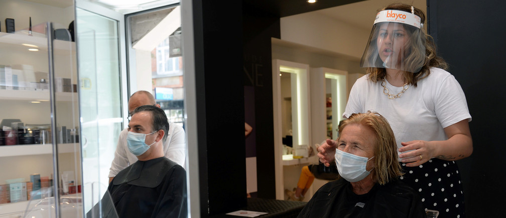A hairdresser wearing a protective face mask cuts the hair of a customer following the outbreak of the coronavirus disease (COVID-19) in Brussels, Belgium, May 18, 2020.REUTERS/Johanna Geron - RC22RG9BQKG2