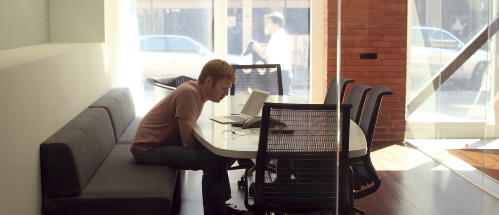 An employee conducts a conference call at the headquarters of Web-building service Weebly in San Francisco, California February 28, 2013. Working from home is common enough in the Valley, but that is in addition to - not instead of - the 40-plus hours spent working in the office. Despite the area's image as a freewheeling space that makes much of the technology that allows people to work remotely, Bay Area workers tend to head into the office, especially at start-ups. Weebly CEO and founder David Rusenko says it simply becomes more efficient for everyone to sit together.     REUTERS/Robert Galbraith  (UNITED STATES - Tags: SCIENCE TECHNOLOGY BUSINESS) - GM1E9310KAV01